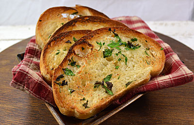 Italian bread with garlic and parsley;A big bold rich Italian Tomato Sauce is not complete without a thick slice of crusty Italian Bread.  This is no mere suggestion, but a prerequisite at dinner tables everywhere.  How else is every drop of the flavorful sauce to be accounted for?